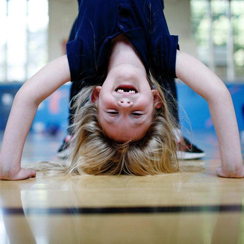 Young girl doing a headstand in a school gymnasium