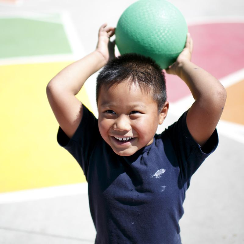 young boy about to throw a rubber ball on a playground
