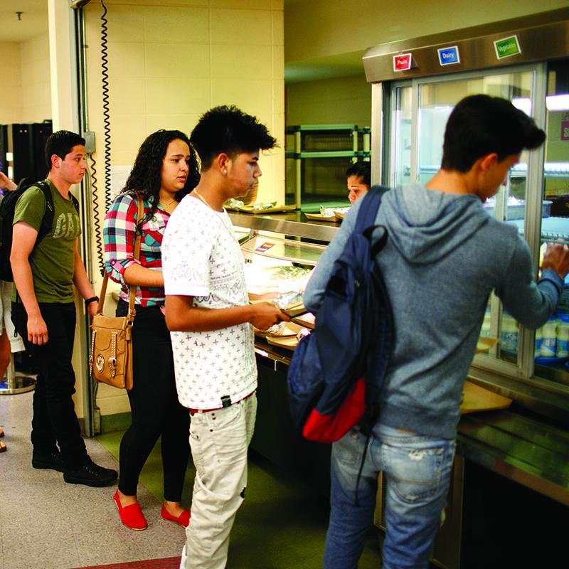 students lined up at the school cafeteria to get their afterschool meal