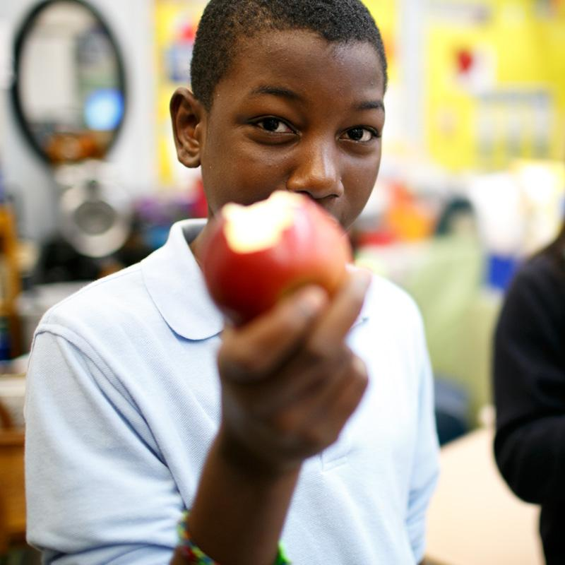 Teenage boy eating an apple holds up apple to camera while chewing