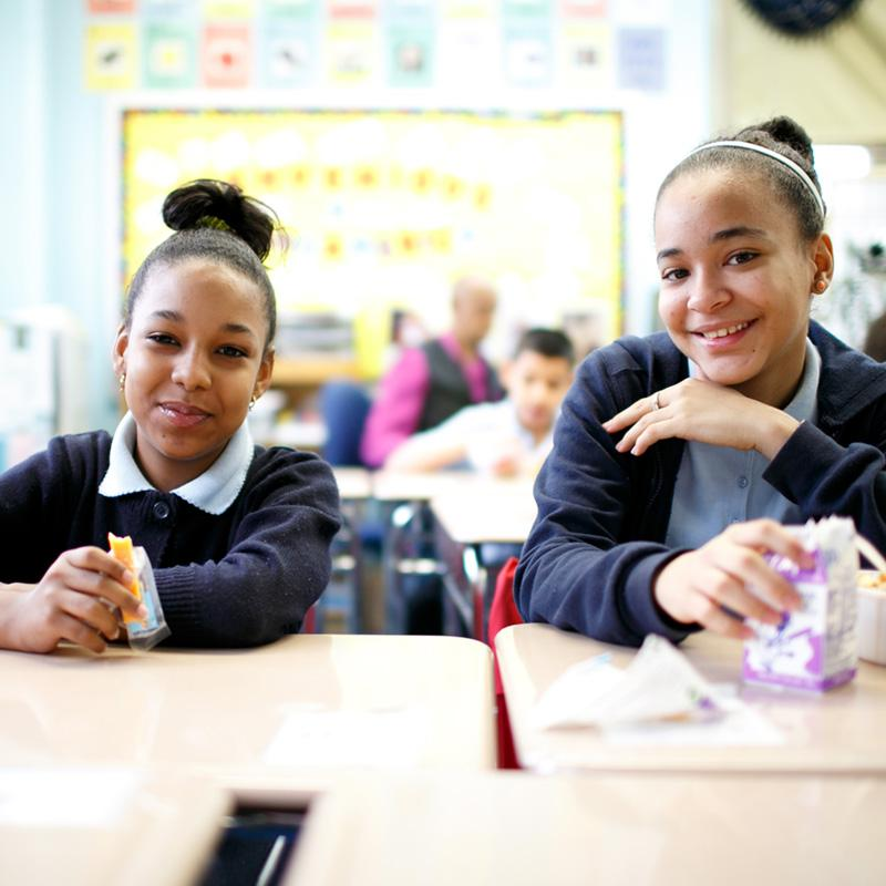 two teenage girls sitting at their school desks smiling into the camera while they eat their breakfast