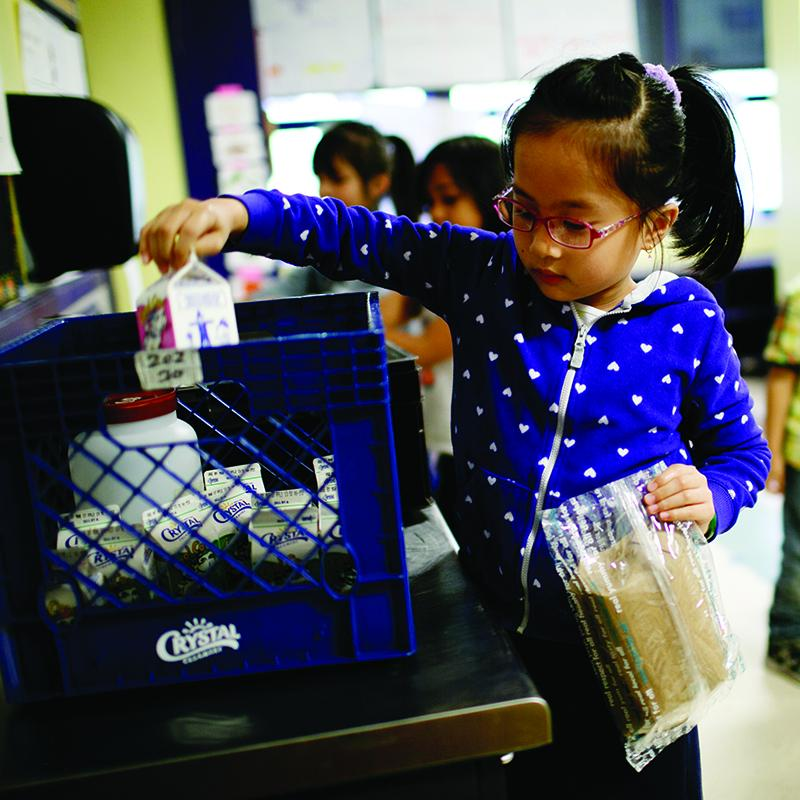 young girl taking milk out of a crate in her classroom
