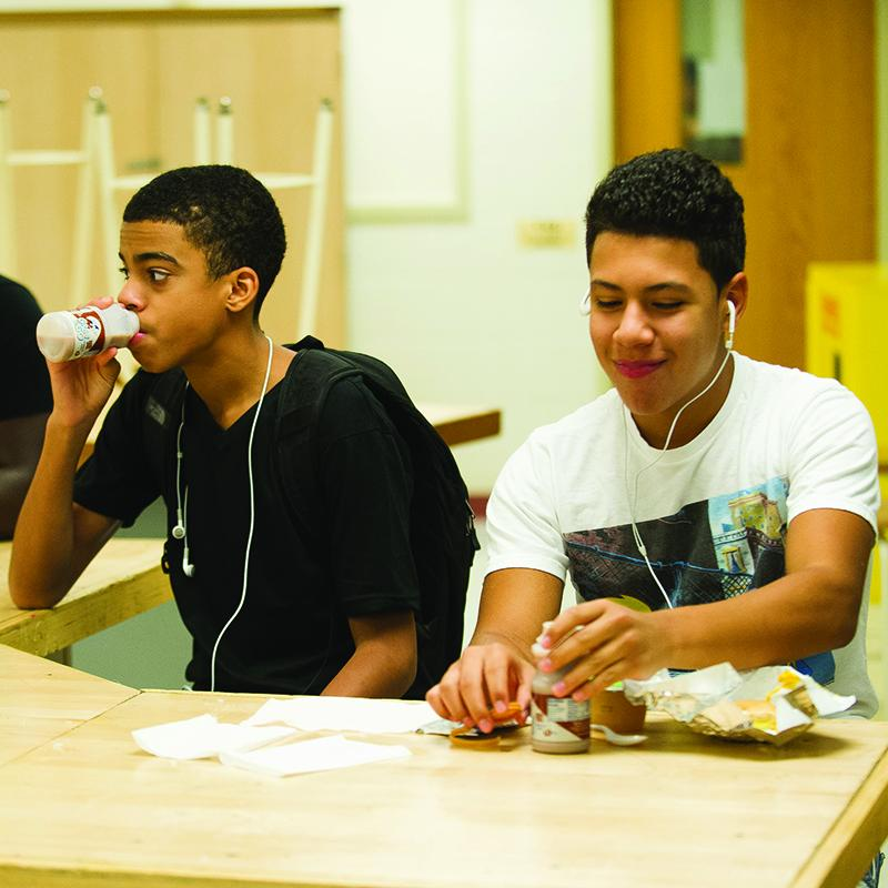 two teenage boys sitting in class, eating their breakfast