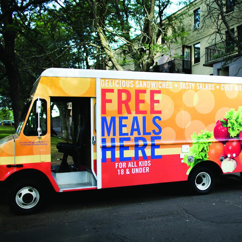 "Colorful van with text that says ""Free Meals Here"""