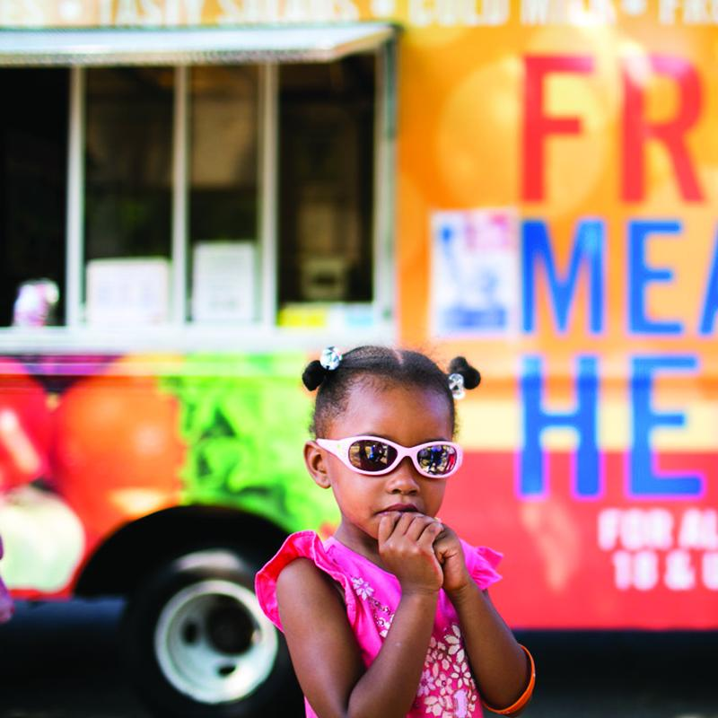"young girl with sunglasses stands in front on a truck that reads ""free meals here"""