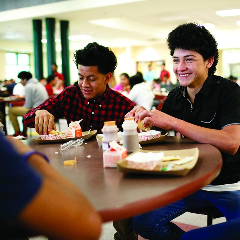 two teenage boys eating a meal at school