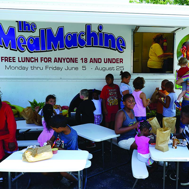 kids eating at tables that are placed in front of a mobile meals delivery truck