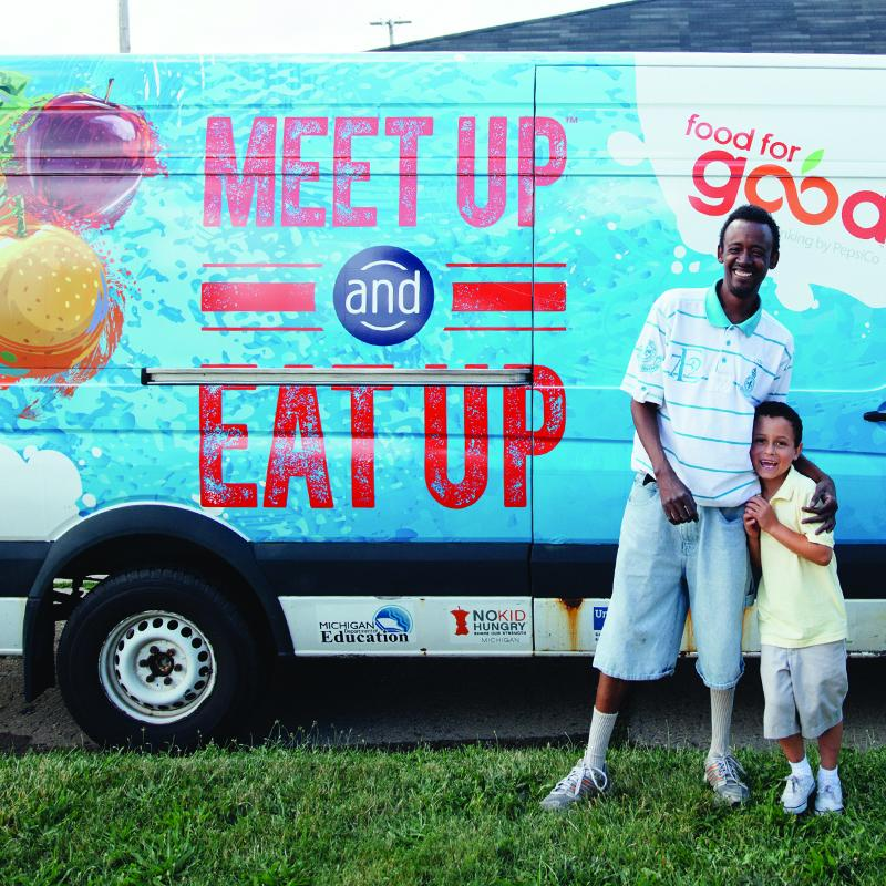 man and boy standing in front of van that gives out summer meals