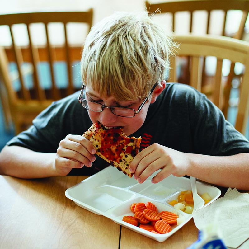 boy eating pizza from his afterschool meals