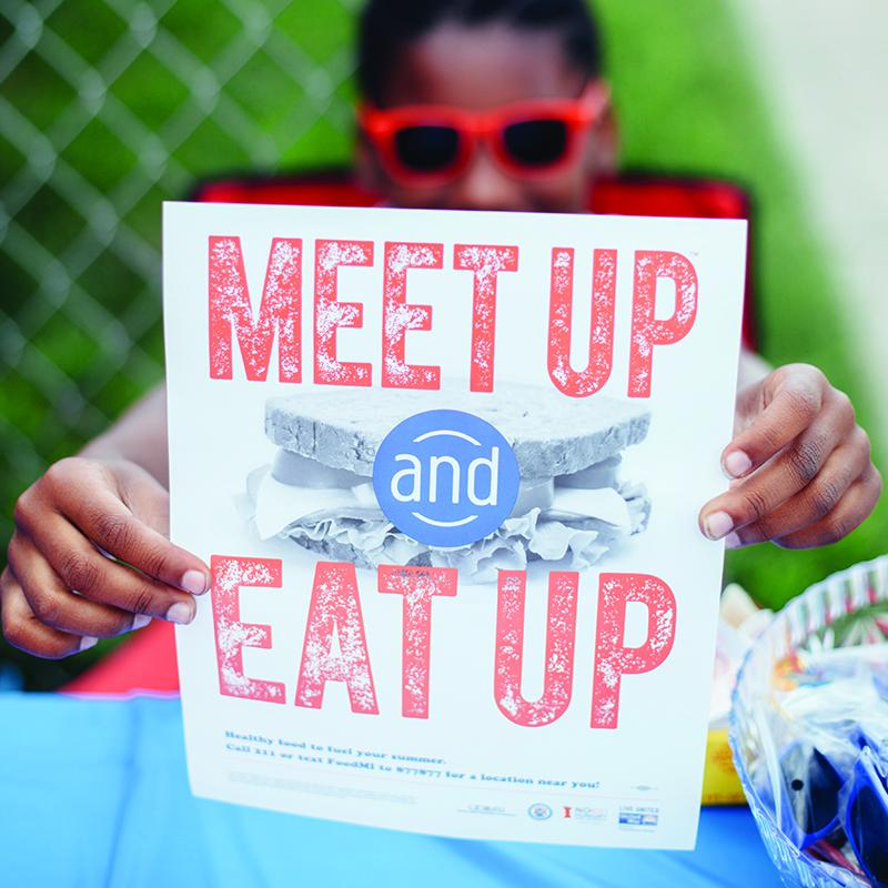 "kid holding a sign that says ""Meet up and eat up"""
