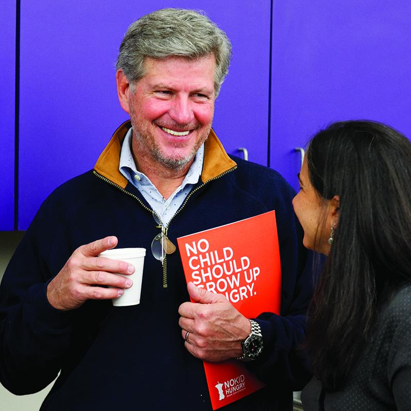 Man smiling and chatting with a women while holding a No Kid Hungry folder