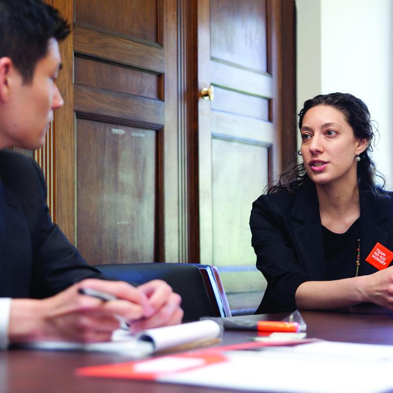 two adults in conversation at a capital building