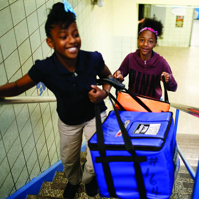 two 5th-grade girls taking coolers full of breakfast food up a flight of stairs to their classroom