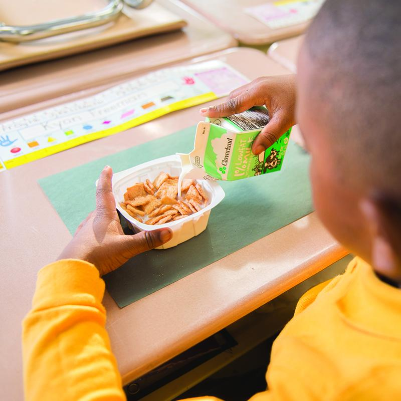 elementary school boy pouring milk onto his cereal at his classroom desk