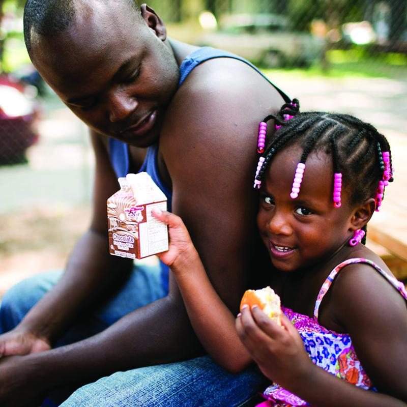 father with his young daughter at a summer meals site. the daughter is holding a milk and a roll.
