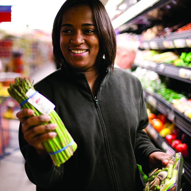 woman in grocery store holding asparagus, and smiling