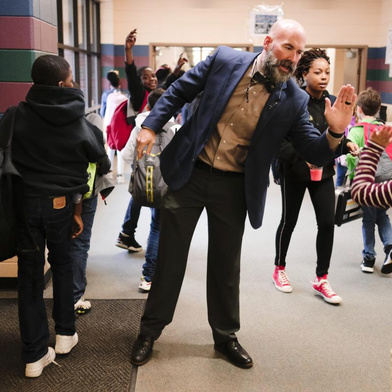 principal giving students high fives