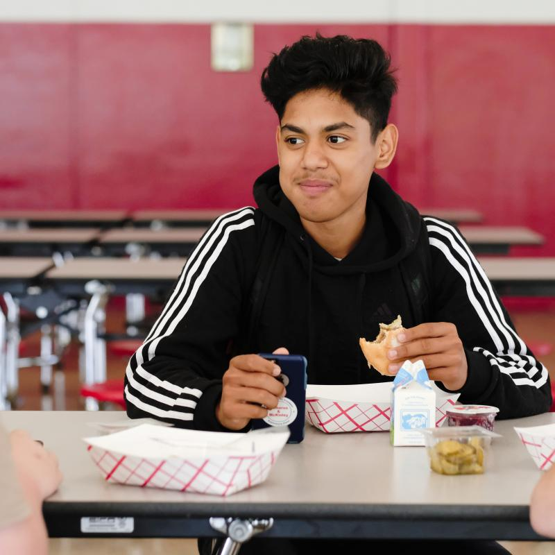 High school student eating afterschool meal in the school cafeteria
