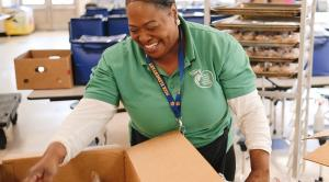 School Nutrition Employee Smiles While Preparing Food