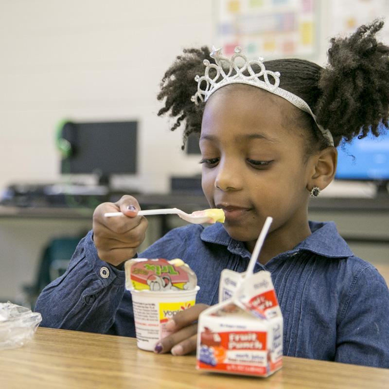 Young girl wearing a tiara is eating yogurt as a snack