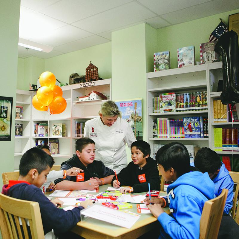 chef chatting with students at a table while they eat and afterschool meal