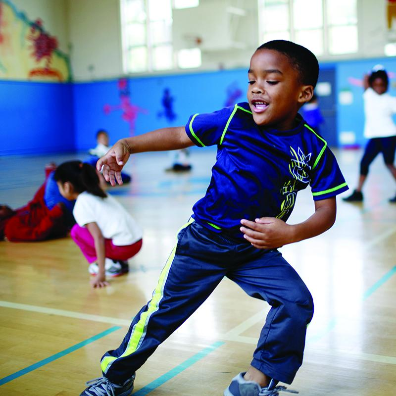young boy doing athletic moves in a gymnasium