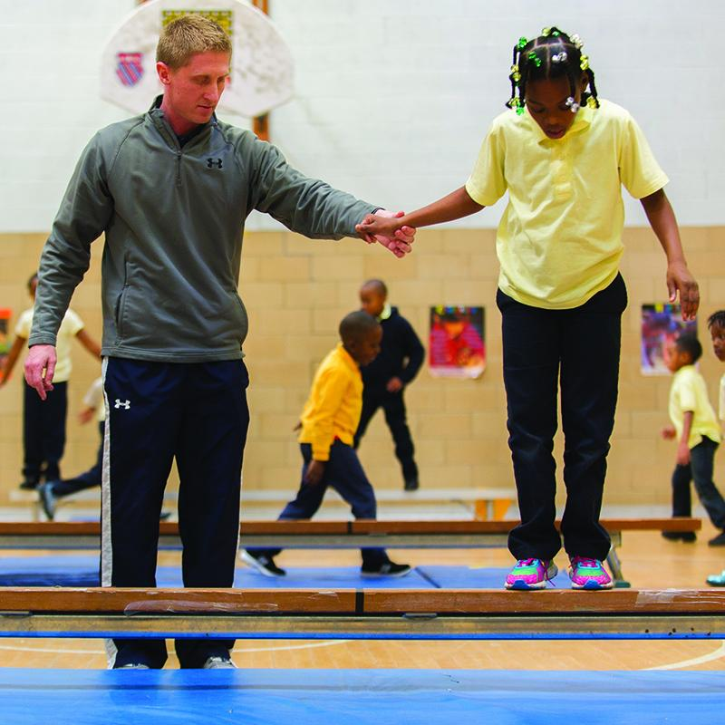 gymnastic coach assisting a student on the balance beam