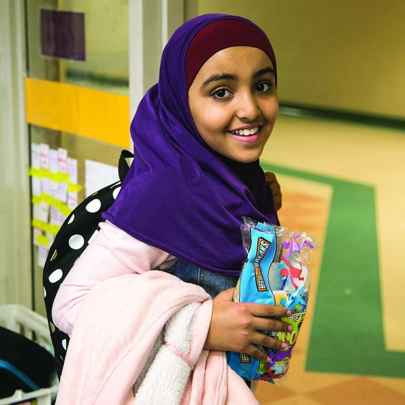 young girl in a hijab leaves her classroom with her afterschool meal