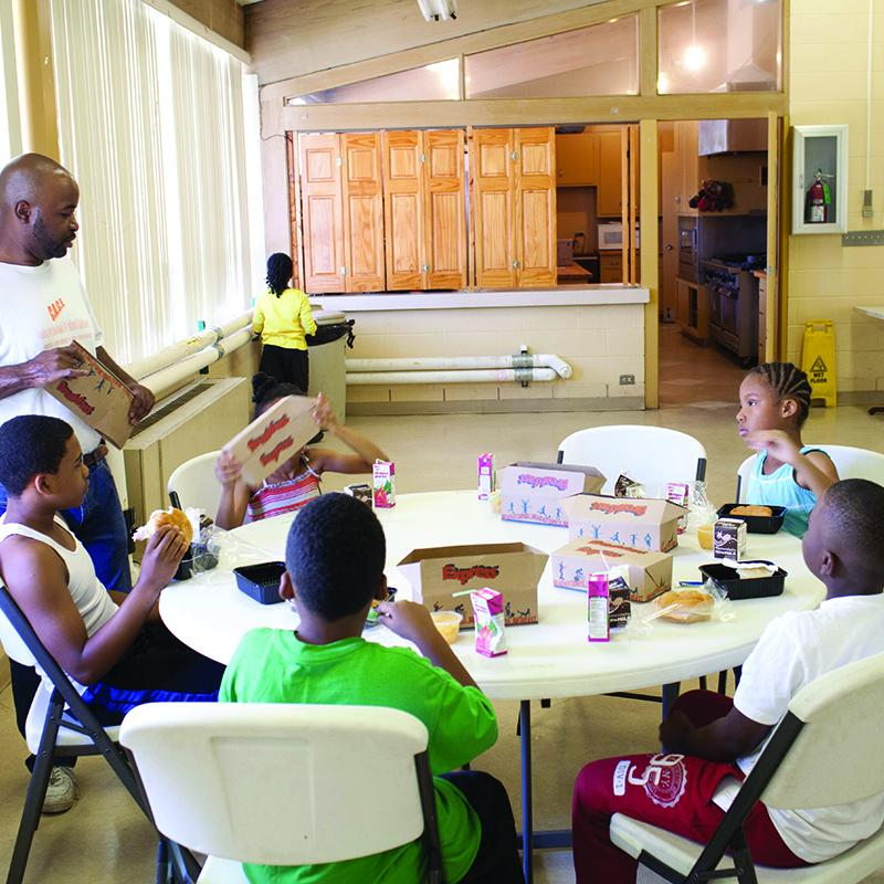 group of kids eating afterschool meals n a community center