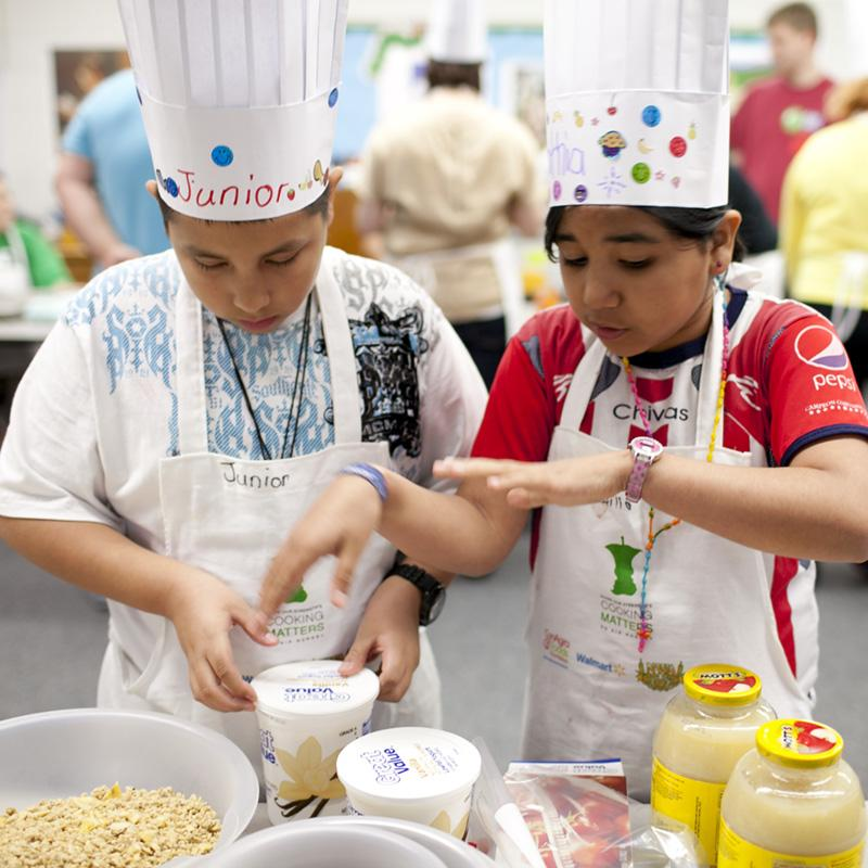 Young boy and girl learning about cooking portion sizes.