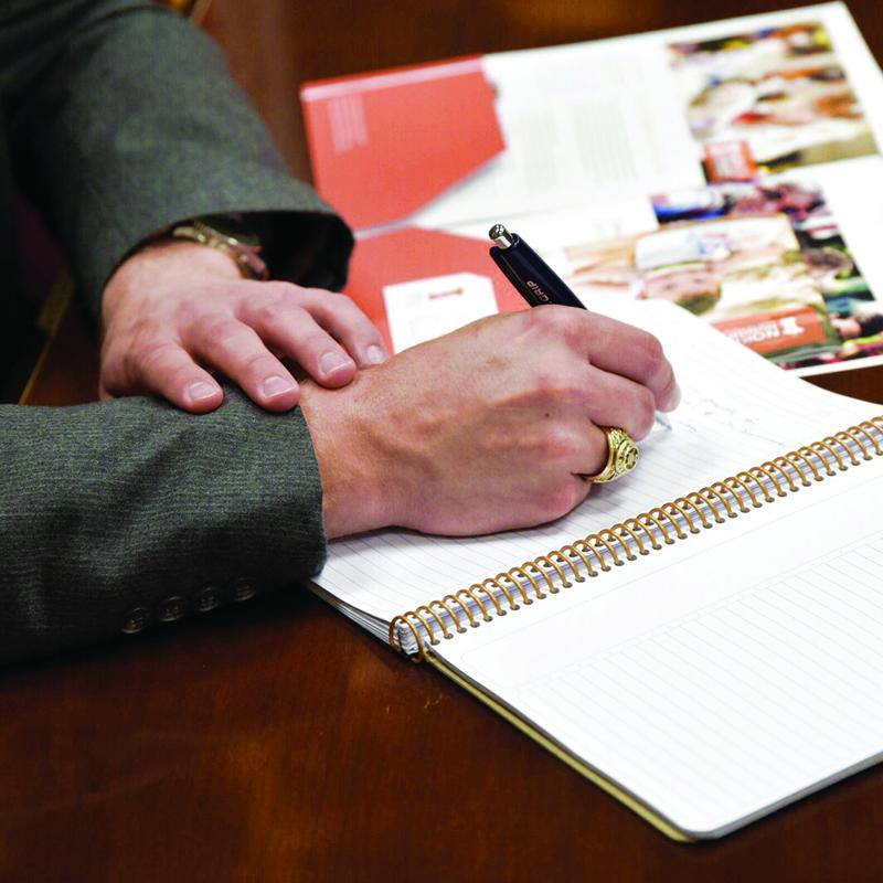 person writing in their notebook during a meeting