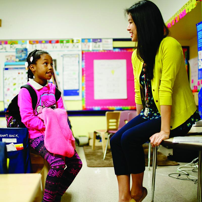 teacher sitting on a desk talking to a young student