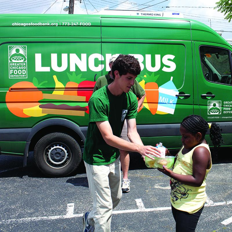 "man giving young girl a meal in front of a truck that reads ""Lunch is on us"""