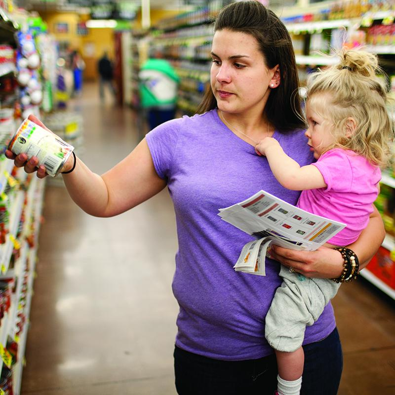 mother holder her toddler in a grocery store shopping for food