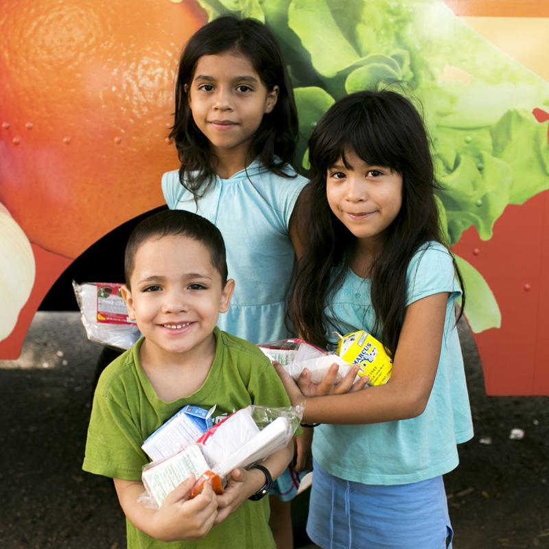 two girls and one boy, all in elementary school, stand holding their summer meal with smiles on their faces
