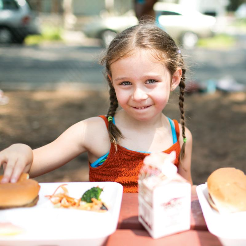 young girl sitting outside at a picnic table grabbing her hamburger about it eat it