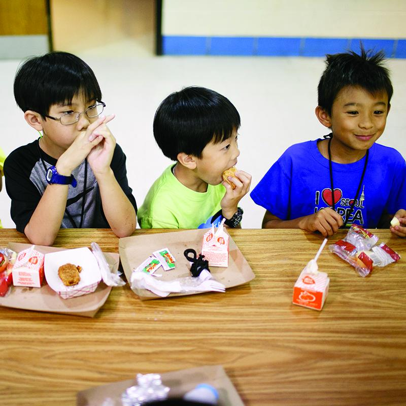 three boys having fun while eating their meal