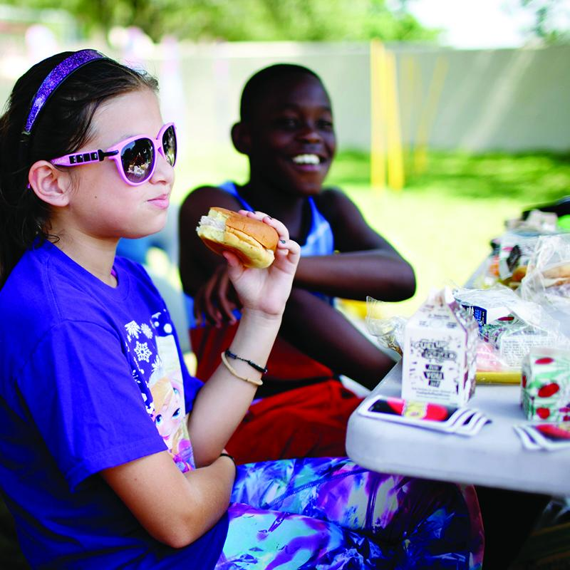 girl wearing sunglasses holds a hamburger in her hand as she socializes with friends at a summer meals site