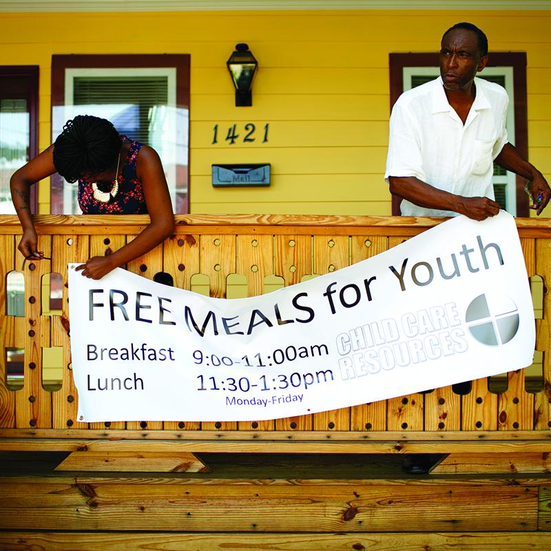 "Two youth center employees hanging a sign outside their building that reads ""Free Meals For Youth"""